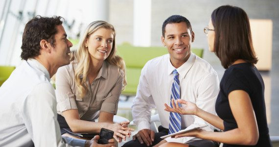 Businesspeople With Digital Tablet Having Meeting In Office